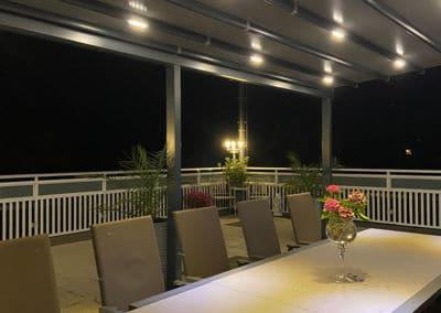 Pergola Terrasse in der Nacht mit Beleuchtung.